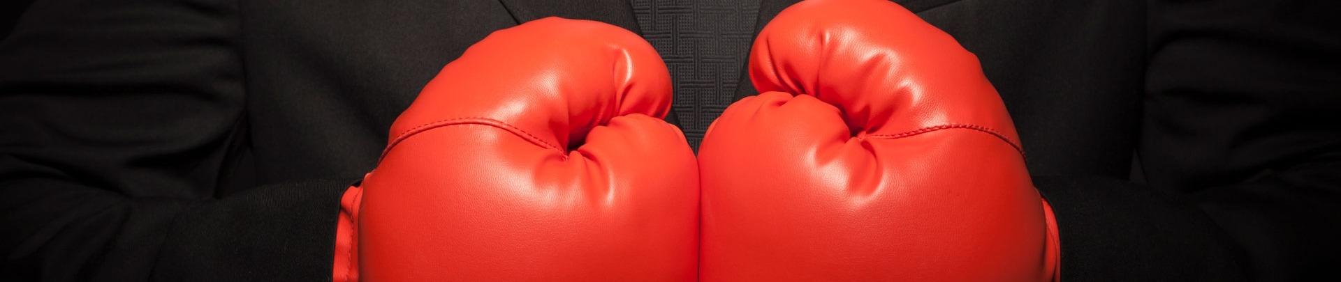Stoere zakenman in zwart pak en rode bokshandschoenen
